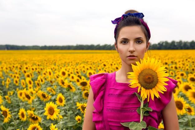 Kobieta w różowej sukience stojącej w polu i trzymającej słonecznik