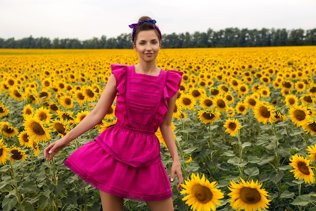 Kobieta w różowej sukience stojącej w polu z słonecznikami w lecie