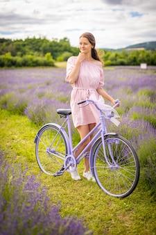 Kobieta w różowej sukience z retro rowerem w lawendowym polu czechy