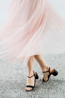 Kobieta w różowej szyfonowej spódnicy tańczy na granitowej podłodze