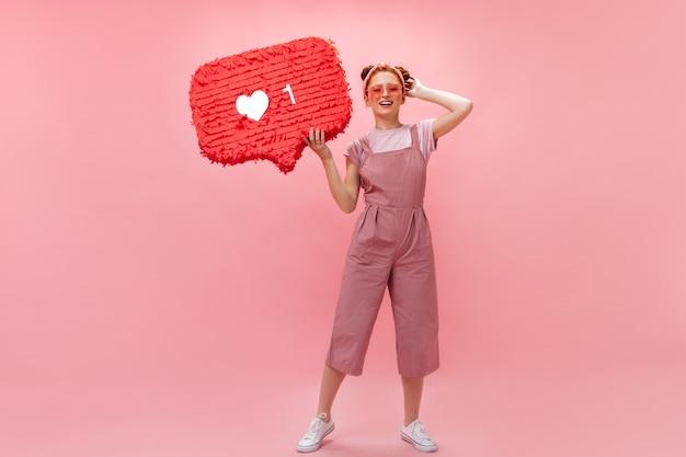 Kobieta w różowych okularach w kształcie serc pozuje z podobnym znakiem. kobieta ubrana w kombinezon i koszulkę uśmiecha się na różowym tle.