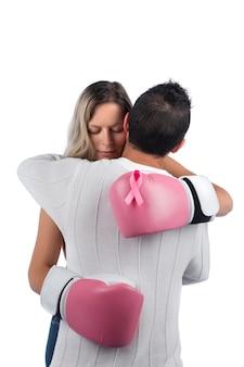 Kobieta w różowych rękawicach bokserskich przytula męża za wsparcie symbolizujące świadomość walki z rakiem piersi