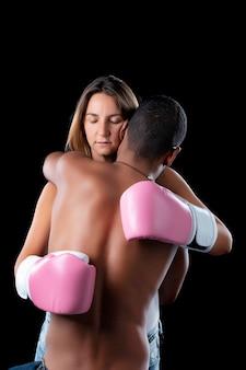 Kobieta w różowych rękawicach bokserskich przytulająca męża za wsparcie, symbolizująca świadomość walki z rakiem piersi