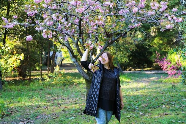 Kobieta w różowym drzewie wiśni. wiosenna rozkosz. wiosna. piękna kobieta cieszy się wiosną.