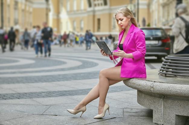 Kobieta w różowym garniturze korzysta z laptopa siedząc na zatłoczonym deptaku.