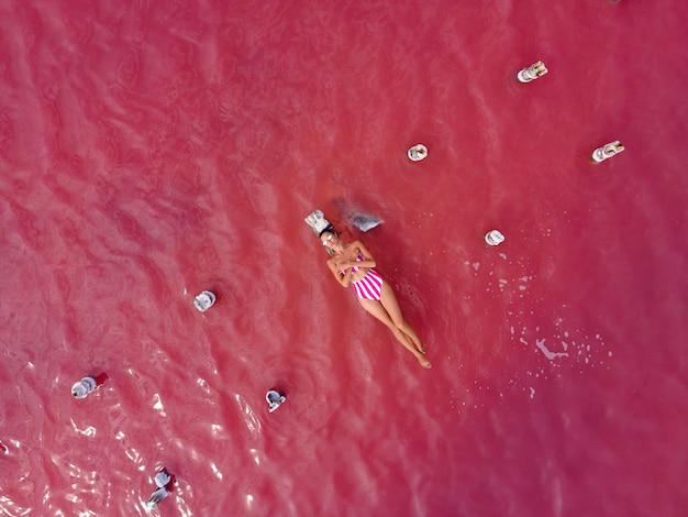 Kobieta w różowym kostiumie kąpielowym leży latem na zrujnowanym drewnianym moście pośrodku różowego jeziora