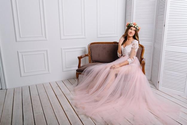 Kobieta w różowym peignoir pozuje w białym studiu