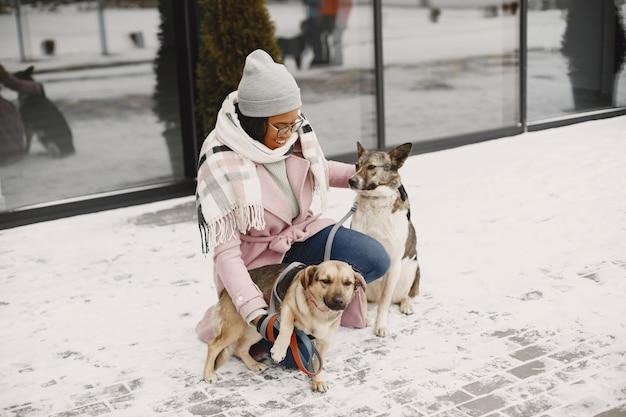 Kobieta w różowym płaszczu z psami