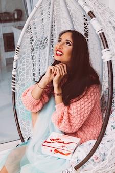 Kobieta w różowym swetrze i niebieskiej spódnicy stoi przy krześle z jajkiem, trzymając pudełko cukierków