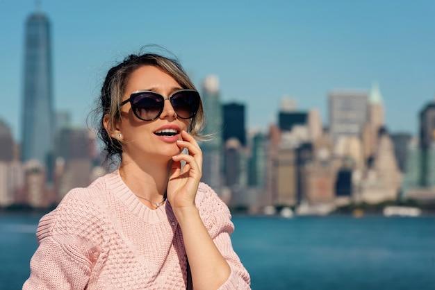 Kobieta w różowym swetrze pozuje w nowy jork