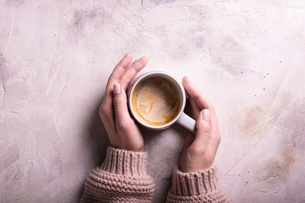 Kobieta w różowym swetrze trzymająca filiżankę kawy leżała płasko