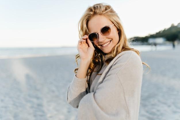 Kobieta w różowym swetrze wkłada brązowe okulary przeciwsłoneczne