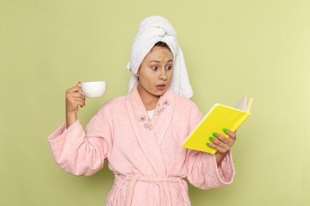 Kobieta w różowym szlafroku czytając książkę