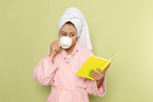 Kobieta w różowym szlafroku picia kawy i czytając książkę