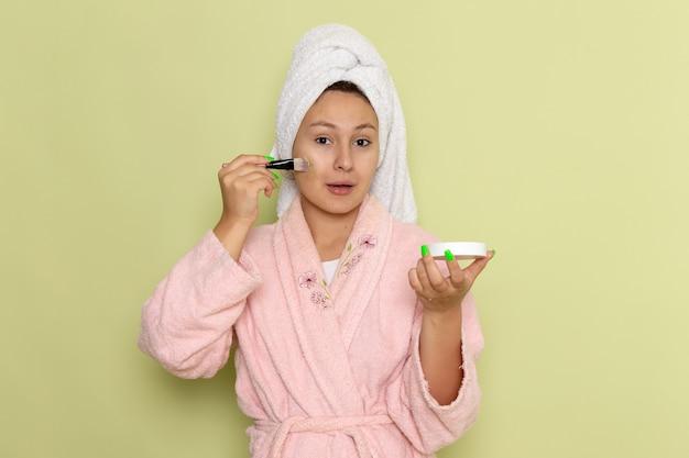 Kobieta w różowym szlafroku robi makijaż