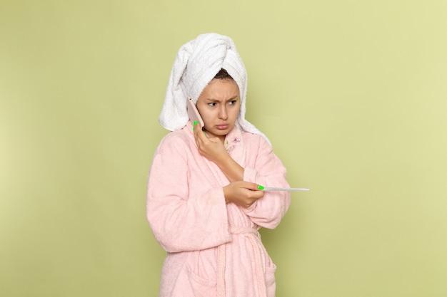 Kobieta w różowym szlafroku rozmawia przez telefon