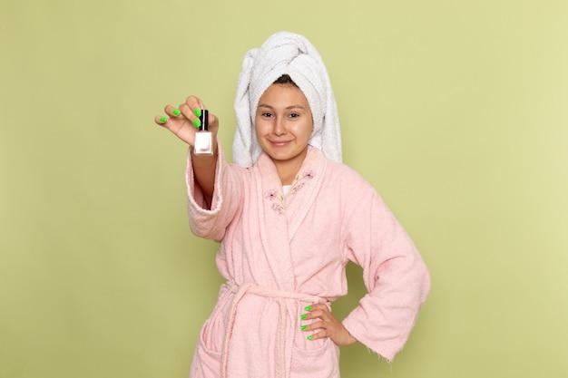 Kobieta w różowym szlafroku trzymając lakier do paznokci
