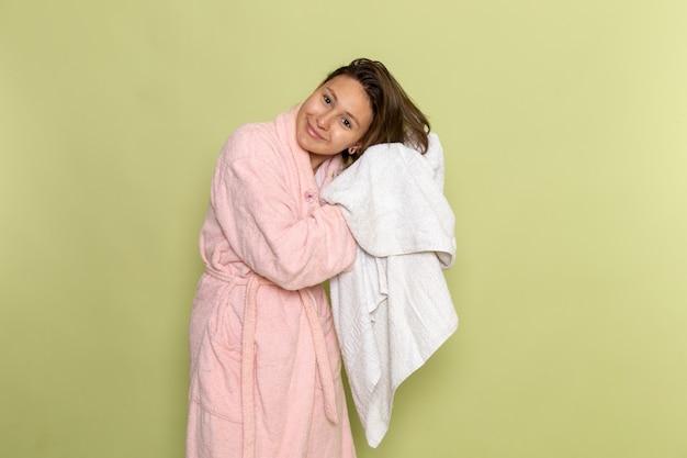 Kobieta w różowym szlafroku, uśmiechając się i suszy jej włosy