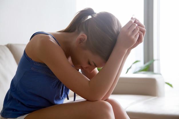 Kobieta w rozpaczy przez rozwód siedzi z pierścieniem