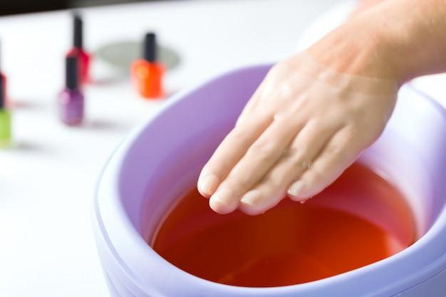 Kobieta w salon paznokci po kąpieli parafinowej