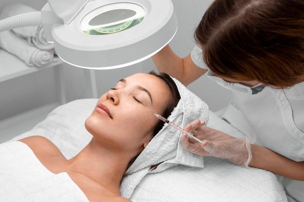 Kobieta w salonie kosmetycznym na zabieg na twarz