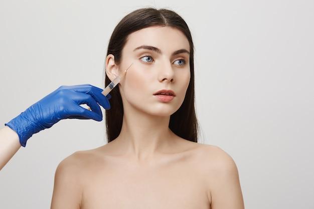 Kobieta w salonie kosmetycznym odwraca wzrok, otrzymuje zastrzyk bottoxu w twarz za pomocą strzykawki
