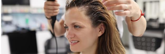 Kobieta w salonie kosmetycznym osusza głowę suszarką do włosów