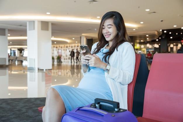 Kobieta w salonie lotniska siedząca na krześle przy oknie i my