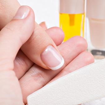 Kobieta w salonie paznokci odbiera manicure. kosmetyczka nakładająca lakier do paznokci na paznokieć.