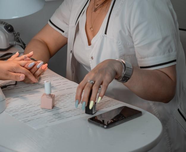 Kobieta w salonie paznokci otrzymująca kosmetyczkę manicure z pilnikiem do paznokci kobieta podczas manicure paznokci