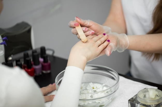Kobieta w salonie paznokci, otrzymująca manicure, kąpie ręce w parafinie lub wosku