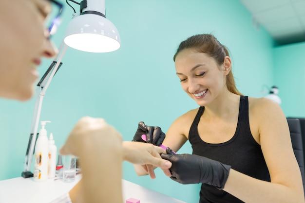 Kobieta w salonie paznokci otrzymujących manicure przez manicurzystę