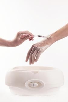 Kobieta w salonie paznokci wykonująca manicure, kąpie dłonie w parafinie lub wosku