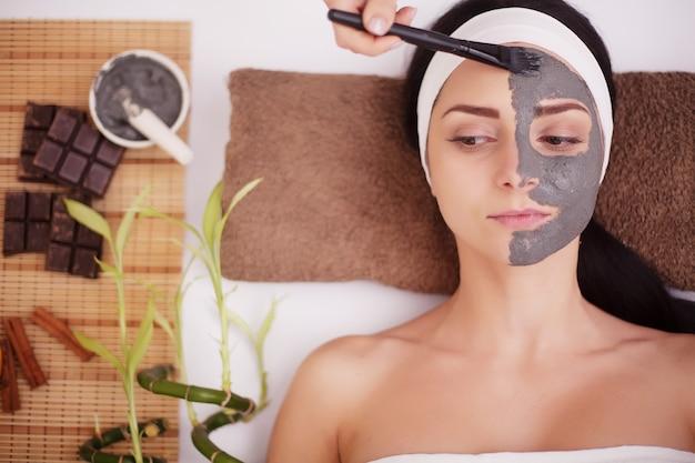 Kobieta w salonie spa z glinianą maską