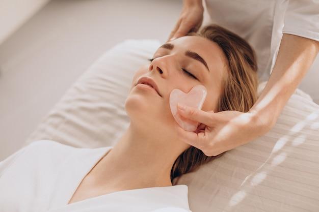 Kobieta w salonie wykonująca zabiegi kosmetyczne z kamieniem gua sha