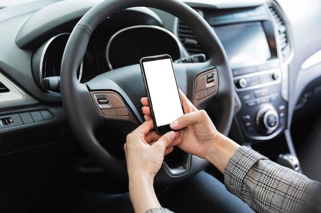 Kobieta w samochodowym mienie telefonu egzaminie próbnym