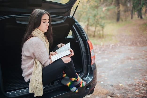 Kobieta w samochodzie, jesień spadek pojęcie. uśmiechnięta ładna dziewczyna czyta książkę rusza się w samochodzie.