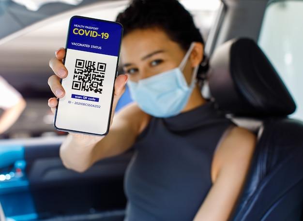 Kobieta w samochodzie nosi maskę na twarz, pokazując ekran smartfona ze statusem szczepienia w paszporcie covid-19 lub koronawirusem i znakiem kodu qr, aby pokazać, że już dostała szczepionkę. koncepcja odporności stada.