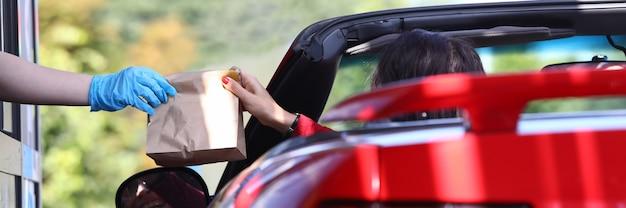 Kobieta w samochodzie podnosi torbę z jedzeniem zbliżenie