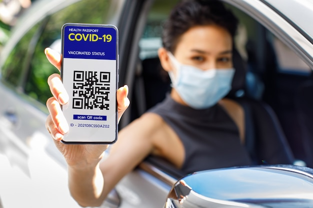 Kobieta w samochodzie pokazuje ekran smartfona ze statusem zaszczepienia w paszporcie zdrowotnym covid-19 lub koronawirusem i znakiem kodu qr, aby pokazać, że już została zaszczepiona. koncepcja odporności stada.