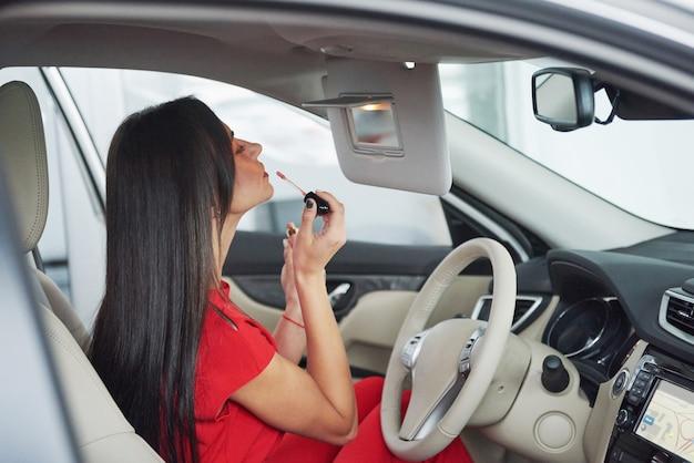 Kobieta w samochodzie utrzymuje koło obracając się wokół uśmiecha się patrząc na pasażerów na tylnym siedzeniu pomysł taksówkarz przed promieniami zachodu słońca światło świeci niebo koncepcja egzaminu pojazd