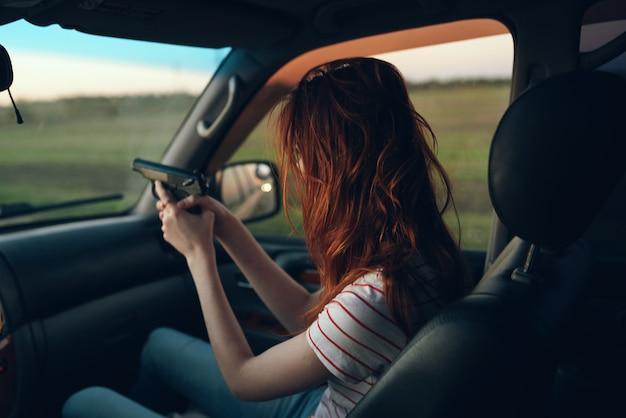 Kobieta w samochodzie z rękami w ręku okno modelu tshirt krajobraz pola