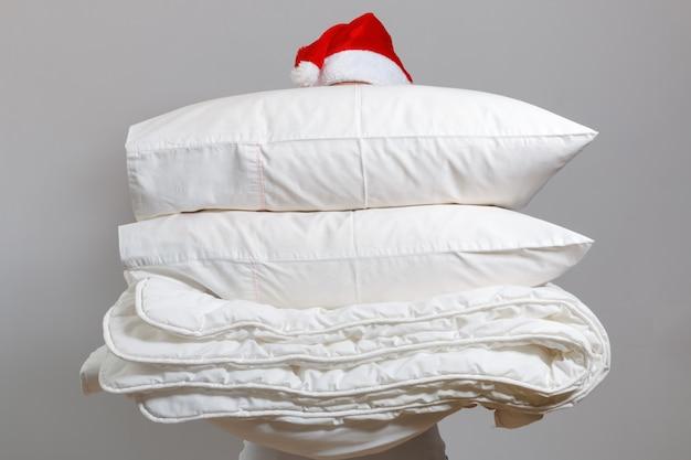 Kobieta w santa hat gospodarstwa ciepłe kołdry i poduszki z piór