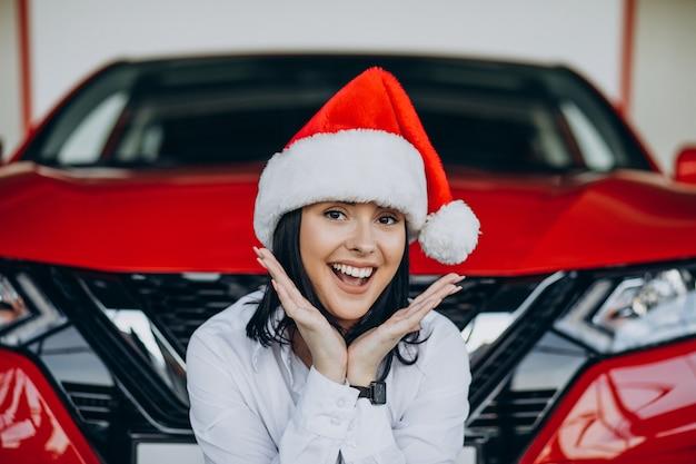 Kobieta w santa hat na boże narodzenie w salonie samochodowym