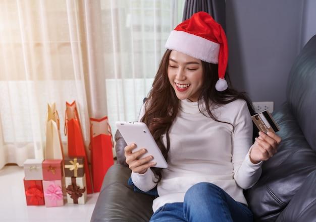 Kobieta w santa hat zakupy online na prezent na boże narodzenie z cyfrowego tabletu w salonie