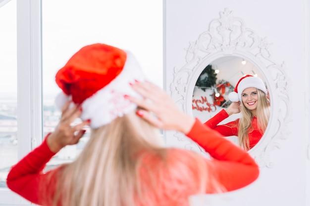 Kobieta w santa kapeluszu patrzeje lustro