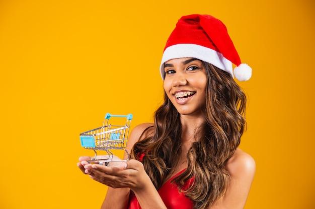 Kobieta w santa kapeluszu robi świątecznym zakupom. pokazuje mini wózek