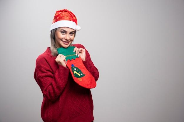 Kobieta w santa kapeluszu trzyma bożonarodzeniową pończochę.