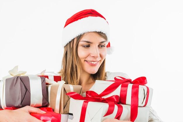 Kobieta w santa kapeluszu z różnymi prezentów pudełkami