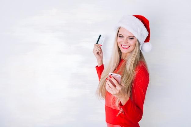Kobieta w santa kapeluszu z smartphone i kartą